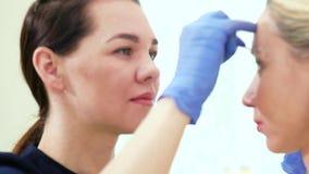 Estetista che prepara le sopracciglia del cliente per microblading video d archivio