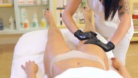 Estetista del primo piano che fa massaggio e l'olio di sfregatura del corpo per una ragazza video d archivio