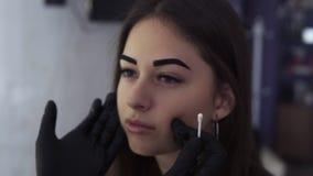 Estetista negli sfregamenti neri della maschera con le sopracciglia di cotone di una donna del tampone, stile la forma Sopraccigl archivi video