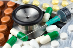 Estetoscópio, comprimidos diferentes e seringa Fotos de Stock Royalty Free