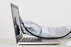 Estetoscópio de Person Hands Checking Laptop With Fotografia de Stock Royalty Free