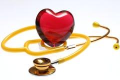 Estetoscópio e coração de vidro vermelho Fotografia de Stock