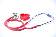 Estetoscópio e coração vermelho para saudável no isolado branco do fundo Fotografia de Stock