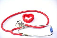 Estetoscópio e coração vermelho para saudável no isolado branco do fundo Foto de Stock