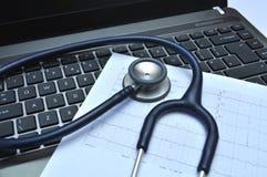 Estetoscópio e electrocardiograma em um portátil fotos de stock