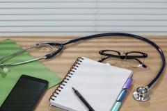 Estetoscópio e um bloco de notas que coloca em uma mesa dos doutores Imagens de Stock