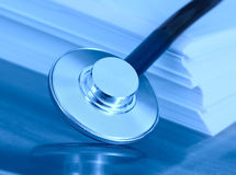 Estetoscópio e uma pilha de papel. O conceito do legisla médico Imagens de Stock