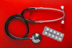 Estetoscópio médico da cor preta e dos comprimidos no frasco no fundo vermelho limpo Disposição para o desenhista Foto de Stock