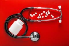 Estetoscópio médico da cor preta e dos comprimidos no frasco no fundo vermelho limpo Disposição para o desenhista Fotos de Stock