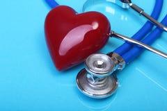 Estetoscópio médico e coração vermelho no fundo azul do espelho Foco seletivo Imagens de Stock Royalty Free