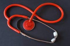 Estetoscópio médico vermelho no fundo preto Instrumento médico Fotos de Stock Royalty Free