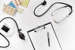 Estetoscópio no escritório dos doutores Vista superior da tabela da mesa do ` s do doutor, papel vazio na prancheta com pena Copi Fotografia de Stock Royalty Free
