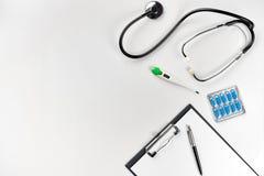 Estetoscópio no escritório dos doutores Vista superior da tabela da mesa do ` s do doutor, papel vazio na prancheta com pena Copi Foto de Stock