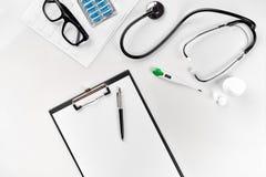 Estetoscópio no escritório dos doutores Vista superior da tabela da mesa do ` s do doutor, papel vazio na prancheta com pena Copi Fotos de Stock Royalty Free