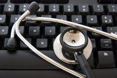 Estetoscópio por um teclado de computador fotografia de stock royalty free