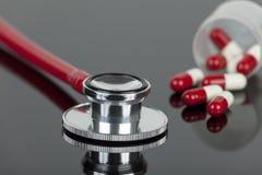 Estetoscópio vermelho no worktop do laboratório com as cápsulas derramadas do comprimido Imagens de Stock