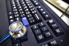 Estetoscopio azul en el teclado Imagenes de archivo