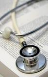 Estetoscopio blanco en un libro médico Foto de archivo