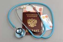 Estetoscopio con el pasaporte, el dinero y la política del seguro médico encendido Imagen de archivo libre de regalías