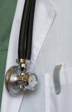 Estetoscopio con el reloj en el delantal del doctor foto de archivo