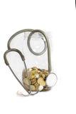 Estetoscopio con las monedas en los ahorros. fotografía de archivo