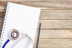 Estetoscopio, cuaderno y lápiz en un backgro de madera ligero de la tabla Foto de archivo libre de regalías