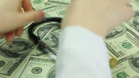 Estetoscopio de la endecha de las manos del doctor en dólares Sistema sanitario corrompido, soborno metrajes