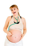 Estetoscopio de la explotación agrícola de la mujer embarazada en su vientre Fotografía de archivo