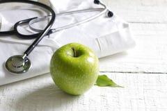 Estetoscopio de la medicina alternativa y fondo verde del símbolo Imágenes de archivo libres de regalías
