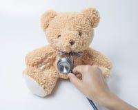 Estetoscopio del corazón del oso de peluche de la atención sanitaria en el fondo blanco fotografía de archivo