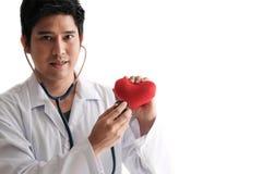 Estetoscopio del uso del doctor de Solated a comprobar encima de corazón Imagen de archivo