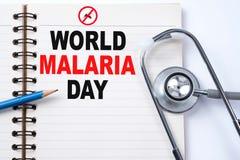 Estetoscopio en el cuaderno y el lápiz con palabras del DÍA de la MALARIA del MUNDO Fotos de archivo libres de regalías