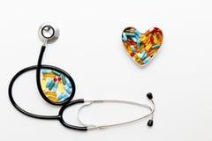 Estetoscopio en el fondo blanco con las píldoras en la forma del corazón Fotografía de archivo