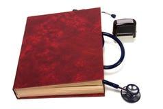 Estetoscopio en el libro rojo Fotos de archivo