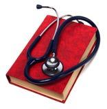 Estetoscopio en el libro rojo Foto de archivo libre de regalías