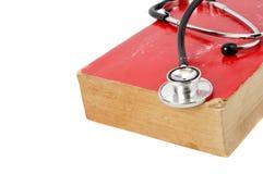 Estetoscopio en el libro viejo rojo Fotografía de archivo libre de regalías