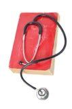 Estetoscopio en el libro viejo rojo Imágenes de archivo libres de regalías
