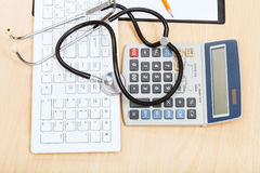 Estetoscopio en el teclado, la calculadora y el tablero Fotos de archivo libres de regalías
