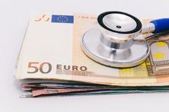 Estetoscopio en una pila de billetes de banco euro Imágenes de archivo libres de regalías