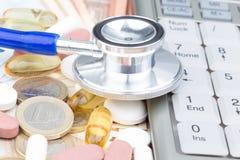 Estetoscopio en una pila de dinero y de píldoras Foto de archivo