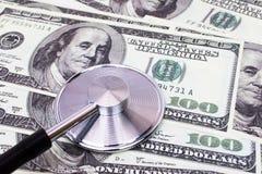 Estetoscopio encima de los dólares de USD que diagnostican la moneda Fotografía de archivo libre de regalías