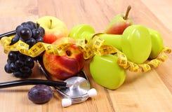 Estetoscopio, frutas y pesas de gimnasia médicos para usar en aptitud Fotos de archivo libres de regalías