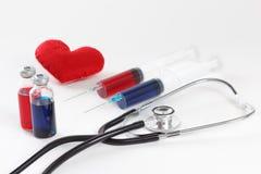 Estetoscopio, jeringuilla y corazón Concepto del cuidado médico Imágenes de archivo libres de regalías