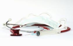 Estetoscopio, jeringuilla y una protección de la boca fotografía de archivo