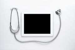 Estetoscopio médico con la tableta de la pantalla en blanco fotos de archivo libres de regalías