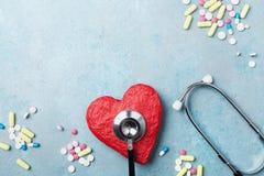 Estetoscopio médico, corazón rojo y píldoras de la droga en la opinión superior del fondo azul Concepto de la presión sana y arte foto de archivo