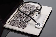Estetoscopio médico sobre el ordenador portátil imagen de archivo libre de regalías