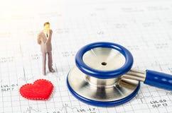 Estetoscopio médico y hombre de negocios miniatura con el corazón rojo Fotografía de archivo