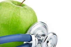 Estetoscopio médico y manzana aislados en blanco Imágenes de archivo libres de regalías