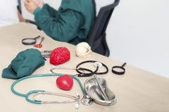 Estetoscopio, modelo rojo del cerebro, modelo humano del cráneo, instrumentos quirúrgicos fotografía de archivo
